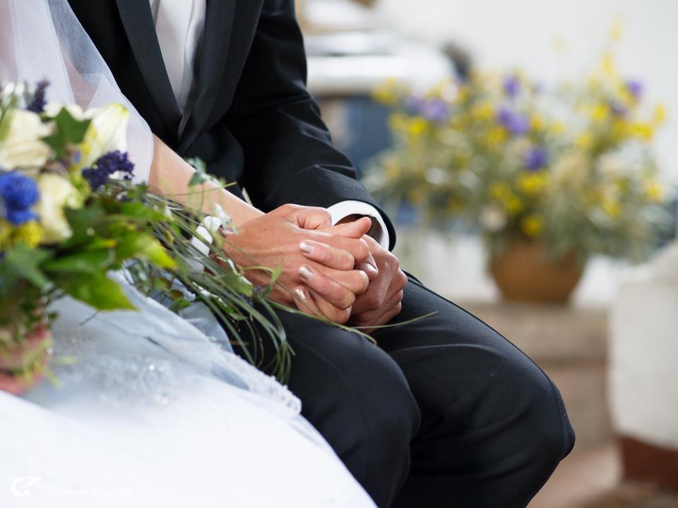 Hochzeitspaar hält Hände in der Kirche