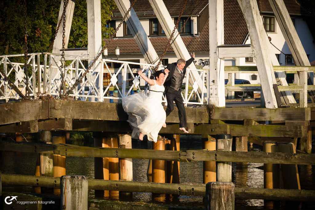 Hochzeitspaar Hand in Hand springt ins Wasser